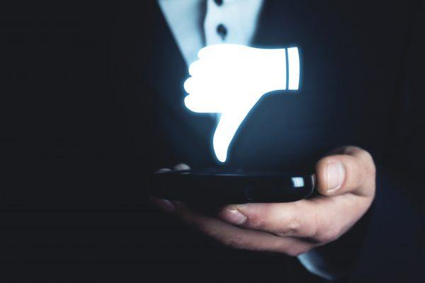 Man holding dislike icon. Social media concept